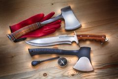 Survival, explore and adventure with compass, axes, knife, fire starter for outdoor life, camping, buschcraft. Axe and knife for survival, travel, camping,many Royalty Free Stock Images
