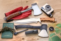Travel, explore and adventure with camera, axes, knife, compass, fire starter for travel, survival and outdoor life. Camera, axes and knife for survival and Royalty Free Stock Photo