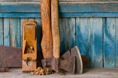 Axes, planer shavings and saw the old blue wooden background.  Stock Photography