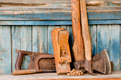 Axes, planer shavings and saw the old blue wooden background.  Royalty Free Stock Images