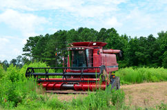 Axial Flow Case lll Combine Harvester. Red Axial Flow Case lll combine harvester sitting on some farmland in the country with some trees and a cloudy blue sky in Royalty Free Stock Photos
