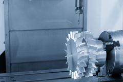 The 5-axis CNC machining center. Cutting the turbine part.The Aerospace part manufacturing process in the light blue scene royalty free stock image