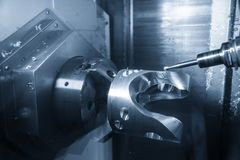 The  5-axis CNC machining center  cutting the automotive part with solid ball end mill. The hi technology manufacturing process of automotive parts stock photos