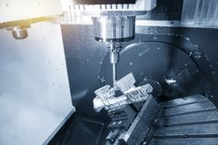 The 5-axis machining centre cutting the aluminium  aerospace part with solid ball  endmill tool. The 5 axis machining center table tilt type machine royalty free stock photography