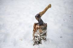 Axt in einer Plattform im Schnee im Winter stockfoto
