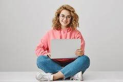 Ayúdeme con la preparación Retrato de la muchacha interesante feliz con el pelo rizado, trabajando en el proyecto, sentándose en  Fotografía de archivo libre de regalías