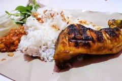 Ayam bakar grillad feg serverd med ris, lalapan och sambal Royaltyfria Bilder