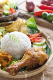 Ayam penyet. Popular delicious Indonesian local food nasi ayam penyet, indonesian fried chicken rice with sambal belacan. Fresh hot with steam smoke stock photo