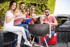 Ayant l'amusement et mangeant des hamburgers dehors Photos stock