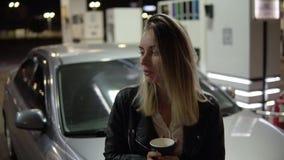 Ayant la jolie femme de sourire de repos se penchant sur la voiture et tenant la tasse de papier noire, café potable Front View banque de vidéos
