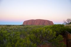 Ayers Rock, Australia at sunset with lots of greenery. Stock Photos