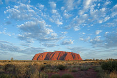 Ayers Rock, Uluru; glowing in morning sun, blue sky with small clouds