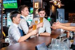 Ayez plaisir à passer le temps avec de la bière Quatre amis buvant la bière et l'ha Photographie stock
