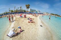 AYIA NAPA CYPR, KWIECIEŃ, - 07, 2018: Ludzie pływa i sunbathing na Nissi plaży Zdjęcie Stock
