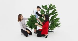 Ayuda asiática de la familia para adornar el árbol de navidad metrajes