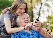 Los jóvenes y la mujer mayor examinan la imagen en teléfono Fotos de archivo