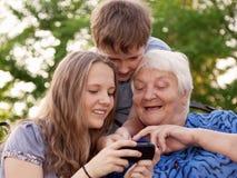 Los jóvenes y la mujer mayor examinan la imagen en teléfono Fotos de archivo libres de regalías
