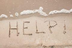 Ayuda de la palabra del mensaje de la escritura en la arena de la playa del mar Fotos de archivo libres de regalías