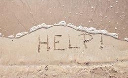 Ayuda de la palabra del mensaje de la escritura en la arena de la playa del mar Imagen de archivo