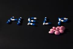 AYUDA de la palabra hecha de píldoras Foto de archivo libre de regalías