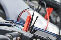 Ayuda del automóvil cables de puente del aumentador de presión que cargan la batería descargada automóvil fotos de archivo libres de regalías