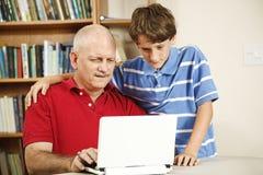 Ayuda del ordenador del hijo Fotografía de archivo