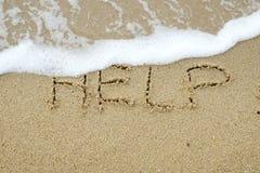 Ayuda escrita en la arena fotografía de archivo libre de regalías
