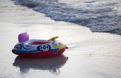 Ayuda inflable de la natación de los niños en la playa en la puesta del sol imágenes de archivo libres de regalías