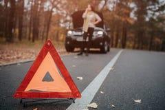 Ayuda y seguro autos, problemas mientras que concepto que viaja Coche quebrado y triángulo auto en el camino, mujer que espera Fotos de archivo