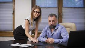 Ayudante atractivo y su jefe La escena en la oficina, un hombre de negocios respetable, canoso y sus jóvenes atractivos almacen de metraje de vídeo