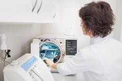 Ayudante de Denatal que usa sistemas de esterilización Instrumentos de la preparación para limpiar fotos de archivo