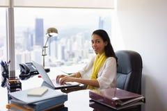 Ayudante de la mujer de negocios que mecanografía en la PC y que sonríe en la cámara Foto de archivo libre de regalías