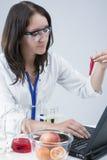 Ayudante de laboratorio femenino con diversos frascos de la prueba que conducen el experimento en laboratorio con la fruta fotos de archivo