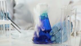 Ayudante de laboratorio que pone el hielo seco en líquido azul en el frasco cónico, haciendo que hierve almacen de metraje de vídeo