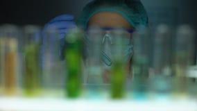 Ayudante de laboratorio que toma el tubo con el líquido azul de la prueba del refrigerador, comprobando la reacción almacen de metraje de vídeo