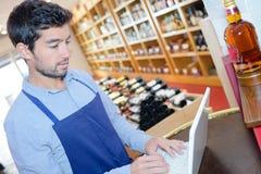 Ayudante de tienda de vino que busca referencia de vino en línea fotos de archivo