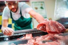 ayudante de tienda en el delantal que clasifica la carne cruda fresca foto de archivo libre de regalías