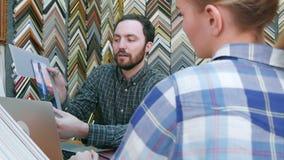 Ayudante de tienda masculino alegre que charla con el cliente femenino, ayudando a elegir el passepartout para el marco en taller almacen de video