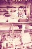 Ayudante de tienda masculino joven que demuestra las salchichas en butcher's Imagen de archivo