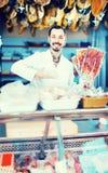Ayudante de tienda masculino que demuestra el tocino cortado en los butcher's sh Fotografía de archivo