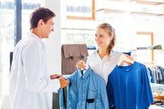 Ayudante de tienda que ayuda a elegir la ropa foto de archivo