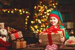 Ayudante del duende de la muchacha del niño de Papá Noel con un regalo de la Navidad imagen de archivo
