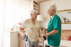 Ayudante del oficio de enfermera que ayuda a la mujer mayor con el marco que camina foto de archivo libre de regalías