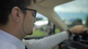 Ayudante del senador en el traje de negocios que conduce el vehículo costoso, yendo al encuentro metrajes