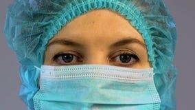 Ayudante enfocado del cirujano que pone la máscara protectora en cara antes de la operación almacen de metraje de vídeo