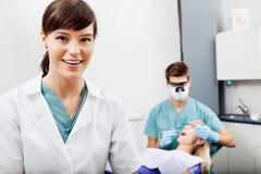 Ayudante femenino con el dentista Working In The foto de archivo