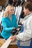 Ayudante femenino de las ventas que da los esquís al cliente Imagen de archivo libre de regalías
