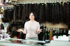 Ayudante femenino de risa que vende pelucas naturales Imagen de archivo libre de regalías