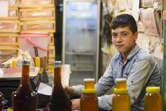 Ayudante joven feliz del vendedor del adolescente en tienda del panal Imagenes de archivo