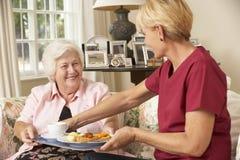 Ayudante que sirve a la mujer mayor con la comida en hogar del cuidado Imagenes de archivo